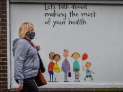 A woman walks past a pharmacy in Merthyr Tydfil (Ben Birchall/PA)