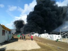Smoke rises from a fire at migrant camp Lipa, Wednesday, Dec 23, 2020, near Bihac in western Bosnia. A huge fire has broken out at a migrant camp in northwestern Bosnia which has been in the focus of rights groups because of poor conditions in the tent facility. Thick black smoke could be seen rising Wednesday from parts of the Lipa camp near the Croatian border which currently houses some 1,200 migrants. The cause of the fire was not immediately known as migrants were seen running away in panic. There were no reports of injuries. (AP Photo/Hasan Arnautovic)
