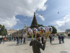 A Palestinian vendor sells balloons in Manger Square, adjacent to the Church of the Nativity in Bethlehem where events have been scaled down because of the pandemic (Nasser Nasser/AP)