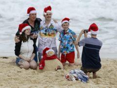 A family pose for a photo on Christmas Day at Sydney's Bondi Beach (Mark Baker/AP)