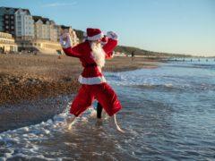 Swimmers in festive costume run into the sea at Boscombe beach in Dorset (Andrew Matthews/PA)