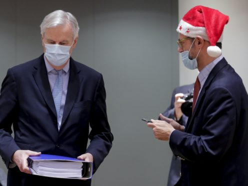 A colleague wears a Christmas hat as European Union chief negotiator Michel Barnier, left, carries a binder of the Brexit trade deal during a meeting at the European Council building in Brussels (Olivier Hoslet, Pool via AP)
