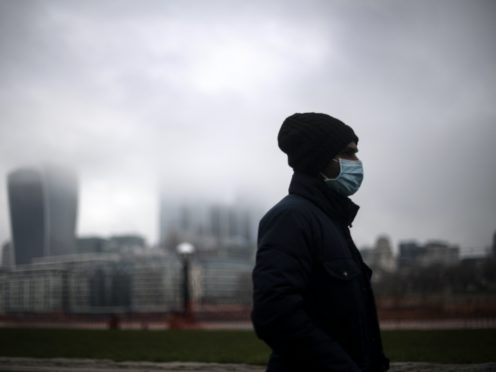 A man wearing a face mask walks past a view of the City of London which is covered in low mist (Victoria Jones/PA)