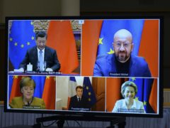 A screen displays Chinese president Xi Jinping, top left, European Council president Charles Michel, top right, European Commission president Ursula von der Leyen, bottom right, French president Emmanuel Macron, bottom centre, and German chancellor Angela Merkel during an EU-China leaders' meeting video conference at the European Council headquarters in Brussels (Johanna Geron, Pool Photo via AP)