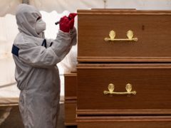 A volunteer marks coffins at Central Jamia Mosque Ghamkol Sharif in Birmingham, which operated as a temporary morgue for the Covid-19 pandemic in April 2020 (Jacob King/PA)