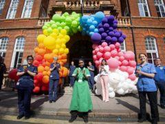NHS staff join the Clap for Carers under a rainbow balloon display (Victoria Jones/PA)