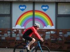 A cyclist passes an NHS tribute painted on a window in Glasgow (Andrew Milligan/PA)