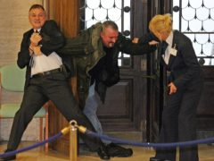 Michael Stone (centre) being restrained by security staff Peter Lachanudis and Susan Porter, as he attempts to storm the Northern Ireland Assembly (PA)