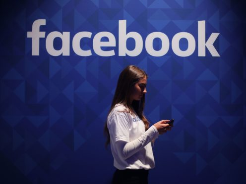 A woman using her phone under a logo of the social media giant Facebook, which has launched a new information centre aimed at providing users with accurate content about climate science in its latest response to online misinformation (Niall Carson/PA)
