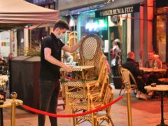 Bar staff pack away chairs and tables in Cardiff (PA)