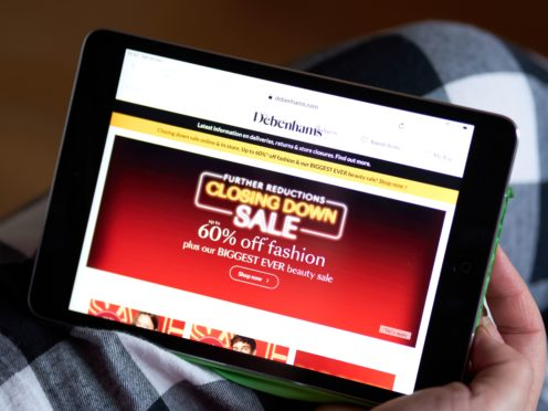 A woman viewing the online offers in the Boxing day sales at Debenhams on a tablet (John Walton/PA)