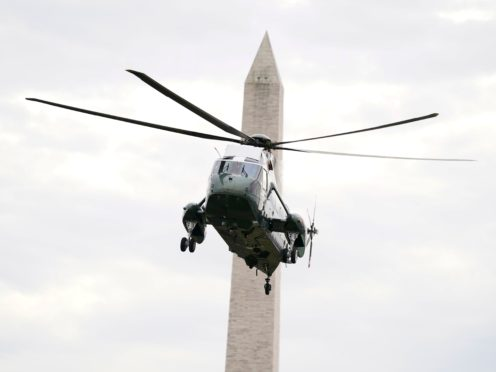 The Washington Monument is seen in the background, as Marine One lands on the South Lawn (Evan Vucci/AP)