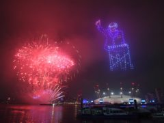 Fireworks erupt behind a drone display of Captain Tom Moore in London's New Year's Eve celebrations (Victoria Jones/PA)
