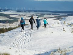 Hikers at Limestone Corner walk along a snow-covered Hadrian's Wall near Hexham, Northumberland (Owen Humphreys/PA)