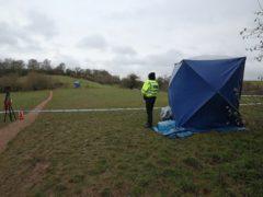 A police officer watches as a forensic tent is set up in Bugs Bottom field in Emmer Green, Reading, where a 13-year-old boy died after being stabbed on Sunday (Jonathan Brady/PA)