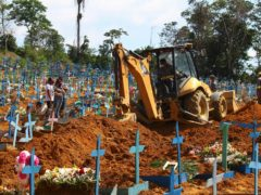 A bulldozer moves earth over a coffin in Manaus, Brazil (Edmar Barros/AP)