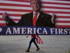 A woman draped in an American flag walks past a banner supporting President Donald Trump (Jae C. Hong/AP)