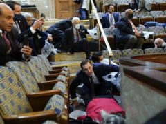 People shelter in the House gallery as protesters try to break into the House Chamber at the US Capitol (Andrew Harnik/AP)