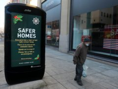 A man walks past an advert for the PSNI's seasons greetings operation on a quiet street in Belfast city centre (PA)