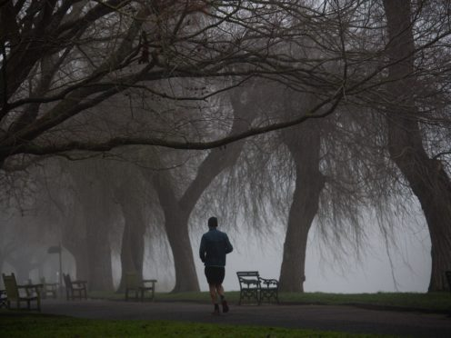 A runner exercises in a cold and foggy St Nicholas' Park in Warwick (Jacob King/PA)