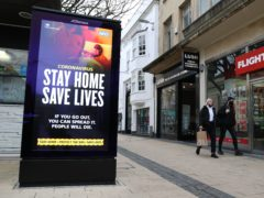 People walk past a 'Stay Home Save Lives' sign on Broadmead in Bristol (Andrew Matthews/PA)