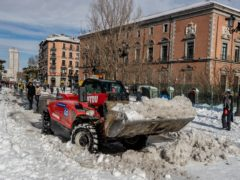 A plough clears snow in central Madrid (Manu Fernandez/AP)