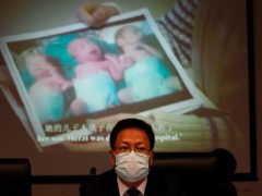 Xu Guixiang, a deputy spokesperson for the Xinjiang regional government, looks up near a slide showing a photo of Uighur infants during a press conference (Ng Han Guan/AP)