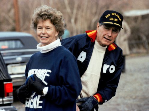 President George H. W. Bush pictured in 1990 hiding behind his sister, Nancy Ellis, as he prepares for a jog along the C&O canal in the Georgetown section of Washington (Marcy Nighswander/AP)