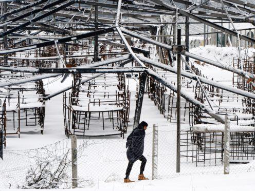 A migrant walks through snow at the Lipa camp, outside Bihac, Bosnia (Kemal Softic/AP)