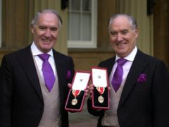 Sir David Barclay, left, and his twin brother Sir Frederick after receiving their knighthoods in 2000 (Michael Stephens/PA)