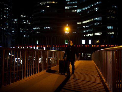 A man wearing a face mask to protect against the spread of the coronavirus wheels a suitcase across a pedestrian bridge in Beijing (Maek Schiefelbein/AP)