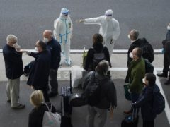 A worker in protective coverings directs members of the World Health Organisation in Wuhan (Ng Han Guan/AP)