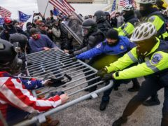 An Arkansas man was accused on Thursday of beating a police officer with a pole flying a US flag during last week's riot at the US Capitol (John Minchillo/AP)