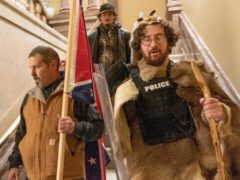 Kevin Seefried, left, walks down the stairs outside the Senate Chamber in the US Capitol with other Trump supporters (Manuel Balce Ceneta/AP)