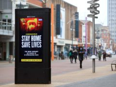 People pass a Stay Home, Save Lives electronic board in Leicester (PA)