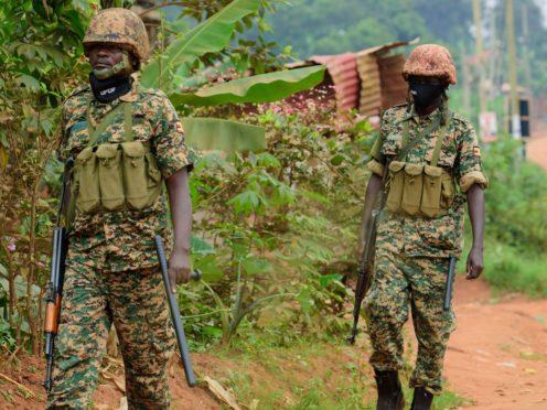 Soldiers patrol outside opposition challenger Bobi Wine's home (Nicholas Bamulanzeki/AP)