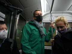 Alexei Navalny, centre, and his wife Yulia travel in an airport bus (Mstyslav Chernov/AP)
