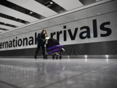 A lone passenger pushes luggage through the arrival hall of Terminal 5 at London's Heathrow Airport (PA)