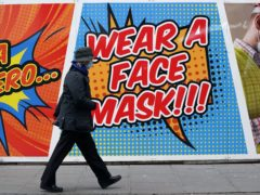 A person walks past a sign telling people to wear a face mask in Nottingham (Zac Goodwin/PA)
