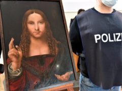 An Italian police officer stands by a copy of the Salvator Mundi in Naples (Italian Police via AP)