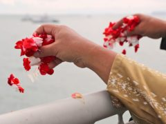 Relatives sprinkle flowers into the Java Sea where Sriwijaya Air flight SJ-182 crashed on January 9 (Tatan Syuflana/AP)