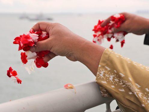 Relatives sprinkle flowers into the Java Sea where Sriwijaya Air flight SJ-182 crashed on January 9 (Tatan Syuflana/AP)