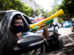 "A demonstrator shouts ""Out Bolsonaro"" while using a noisemaker during a caravan to protest the government's handling of the COVID-19 pandemic and demand the impeachment of Brazilian President Jair Bolsonaro in Rio de Janeiro, Brazil, Saturday, Jan. 23, 2021. (AP Photo/Bruna Prado)"