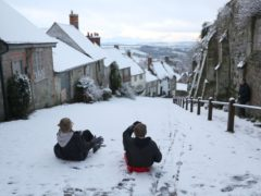 Children sledge down Gold Hill in Shaftesbury, Dorset (Andrew Matthews/PA)