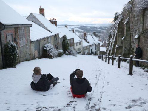 Children sledge down Gold Hill in Shaftesbury, Dorset (Andrew Matthews/PA)