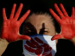 A demonstrator in Brasilia shows her red-painted hands representing the blood of the more than 200,000 deaths from Covid-19 in Brazil (AP)