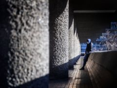 A man wearing a facemask in the Barbican Estate in London (Victoria Jones/PA)