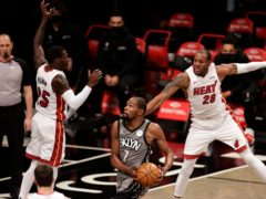 Brooklyn Nets forward Kevin Durant drives to the basket between Miami Heat forward Andre Iguodala and guard Kendrick Nunn (Adam Hunger/AP)