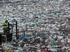 A boat pushes rubbish stuck at the foot of a hydropower plant in Serbia (Darko Vojinovic/AP)