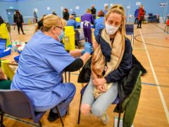 A woman receives the Pfizer vaccine at Cwmbran Stadium (Ben Birchall/PA)